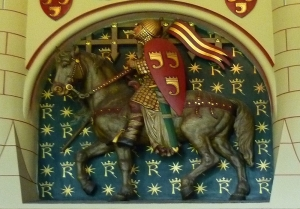 Chimneypiece of the Banqueting Hall, Cardiff Castle, carved by Thomas Nicholls to instructions by the architect William Burges. 1870s. Robert the Consul was the 1st Earl of Gloucester and the 2nd Lord of Glamorgan, the nobleman credited with having built the Norman keep of Cardiff Castle. The main figure on Nicholls's huge chimneypiece depicts this twelfth-century hero setting off on one of his exploits, gazing up at his wife as she waves from the ramparts of a castle, with heralds blowing their trumpets from the castle's ramparts.